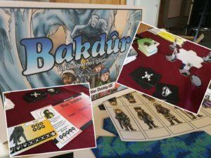 Bilden föreställer lådan till brädspelet Bakadur. På lådan finns en tecknad bild med en grupp barn i äventyrar-kläder som flyr från en vatten-demon. Monterat på det stira fotor finns även mindre bilder på kort, figurer och karaktärsblad från spelet.