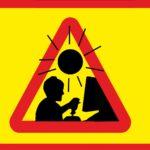 Bilden föreställer en triangulär, rödgul varningsskylt mot en gul bakgrund. På skylten ser man silhuetten av ett barn som spelar datorspel framför en skärm. Ovanför barnet är en svart, stiliserad sol.