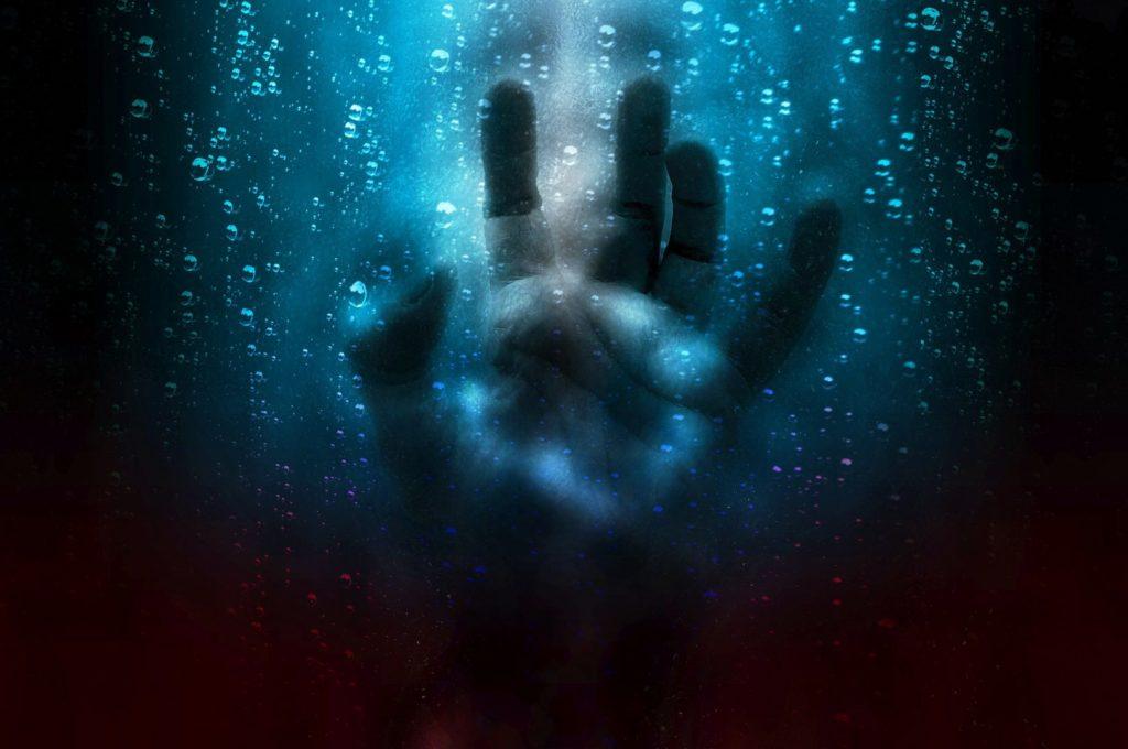 Bilden föreställer en hand som pressas mot insidan på en glasruta. På andra sidan av rutan ser man ett suddigt ansikte och bubbor som rör sig uppåt i mörkt vatten.