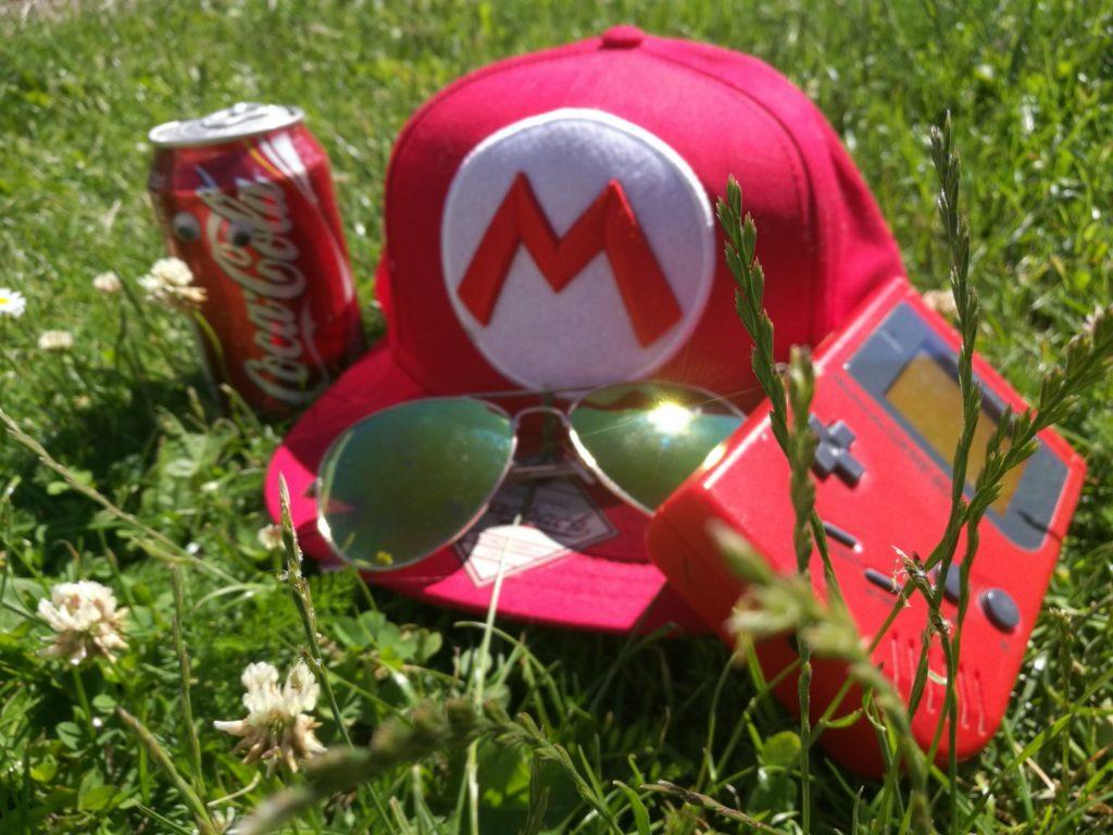 Bilden föreställer en gammal röd Gameboy, en röd Mariokeps, en röd colaburk med ögon på och ett par solglasögon som ligger i grönt gräs.