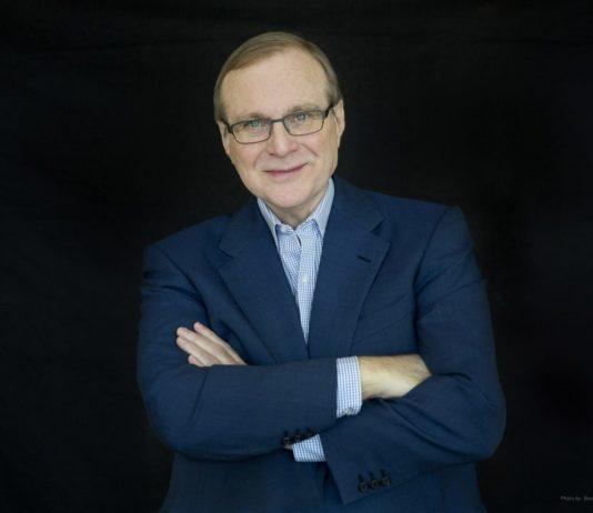 Bilden föreställer Paul G Allen. Han står med armarna i kors, klädd i glasögon och en blå kaval med en ljusblå skjorta under.